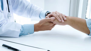 m3 feature doctor holding patient with dementia hand.jpg