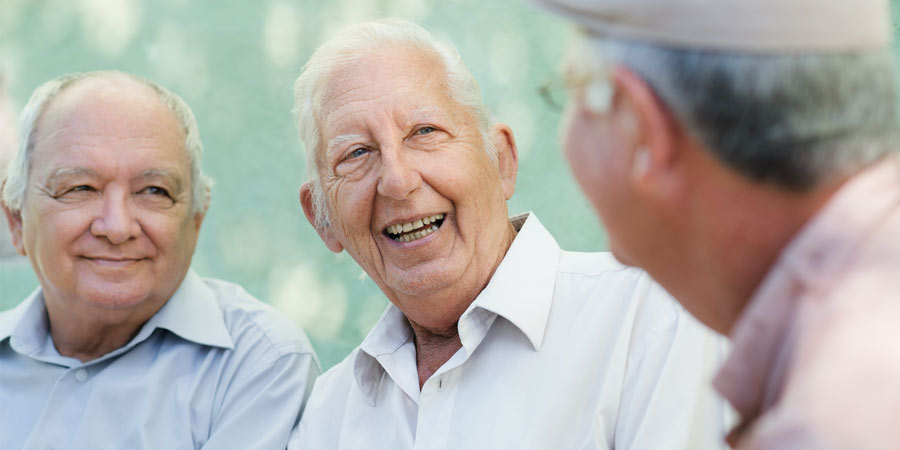 senior man with dementia talking with friends