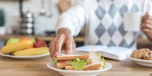 Montessori mealtimes hand going to grab sandwich