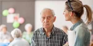 Elderly man with carer holding documents